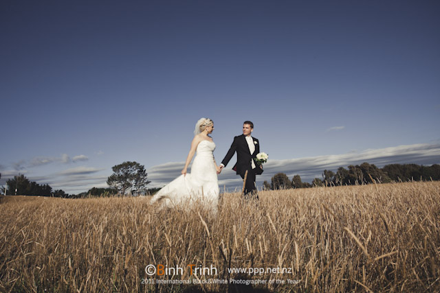 Bride and groom walking through a field in a Palmerston North wedding photo