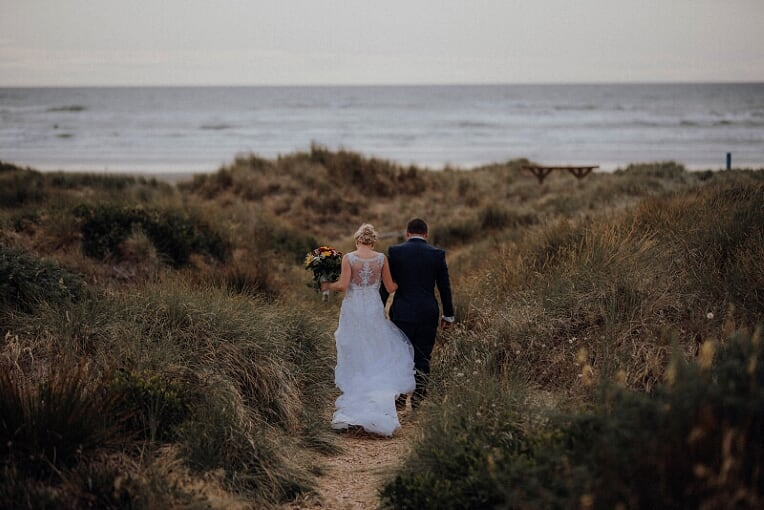 newly married couple walking to the beach