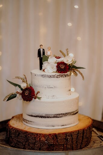 a naked styled wedding cake topped with figurines of the couple