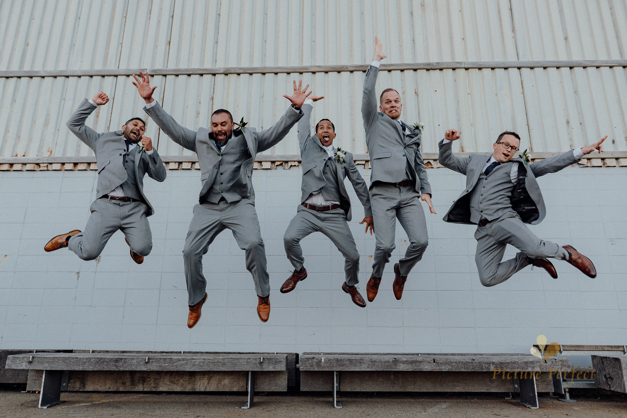 the groom and groomsmen posing for a jumpshot