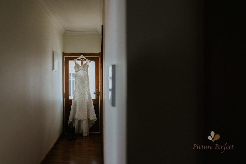 bride dress hanging in door way