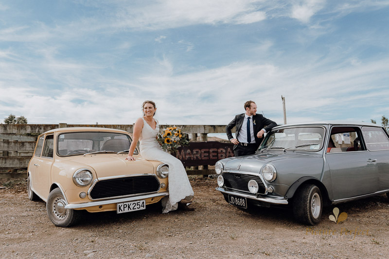 A rustic farm wedding photo of the bride and groom infront of the awesome minis as wedding cars