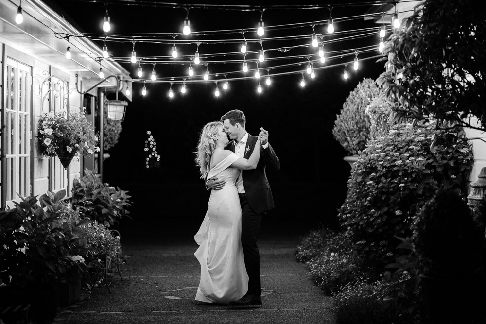 An artistic night wedding photo with the bride and groom dancing under fairy lights