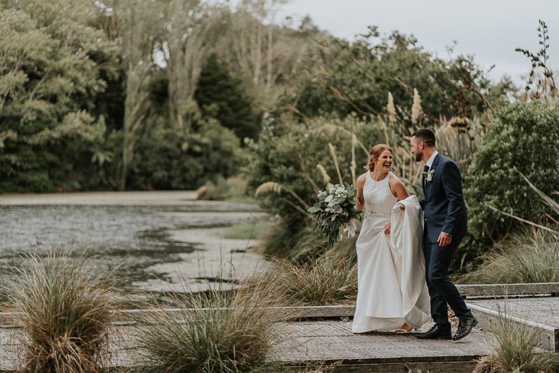 bride and groom walking on walkway at Whanganui park