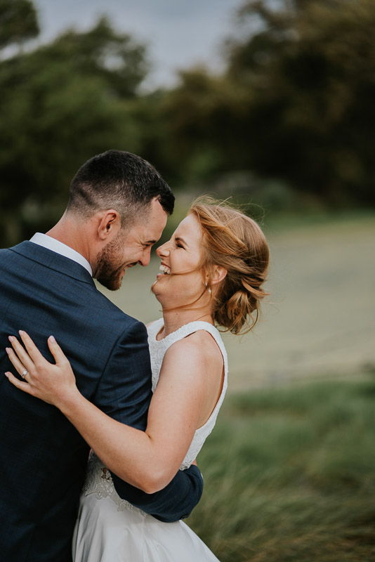 close up wedding image of bride and groom laughing