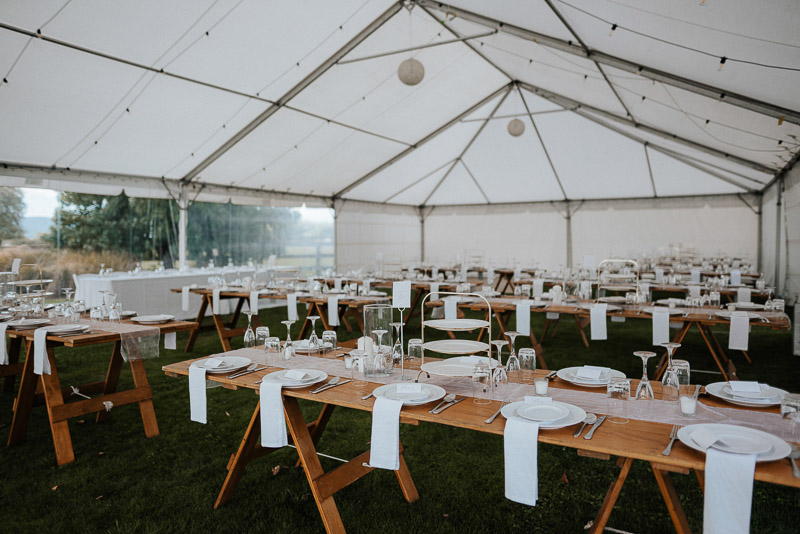 wedding reception setup with wooden tables in marquee