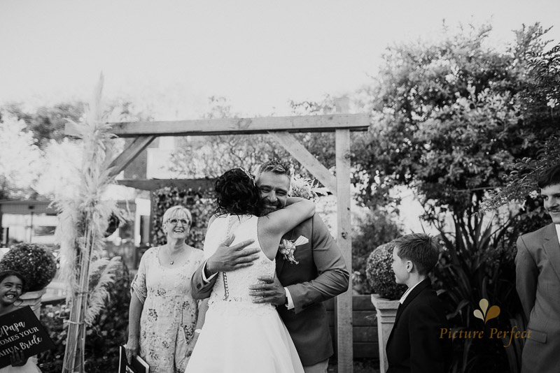 the first hug between bride and groom at whanganui wedding photo with Sherylee