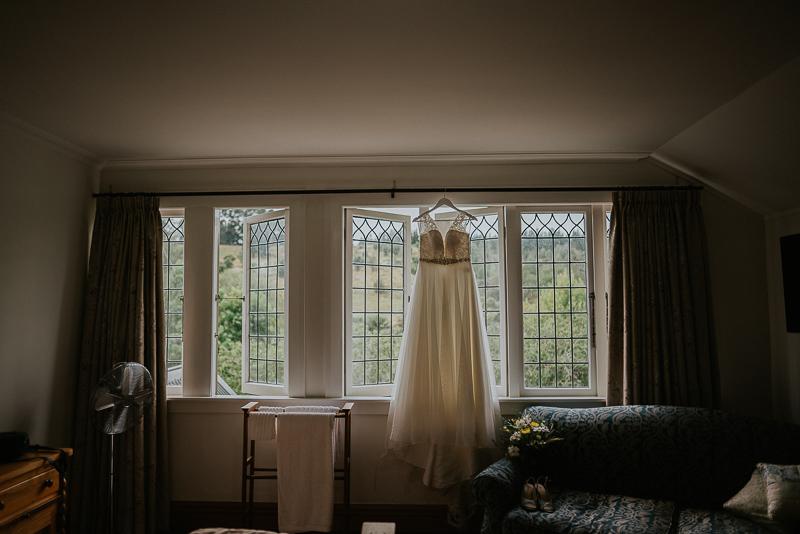 a beautiful wedding dress hang up on the window at Roseburn Park